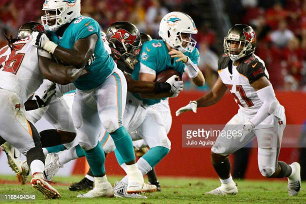Devante Bond of the Tampa Bay Buccaneers wraps up Josh Rosen of the Miami Dolphins for a sack in the second quarter of a preseason football game at...