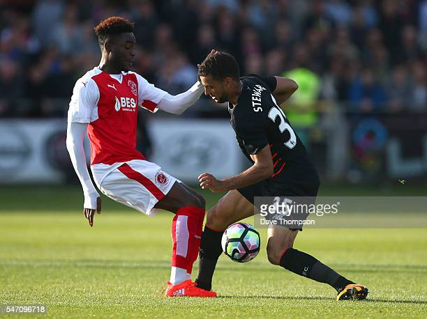 Devante Cole of Fleetwood Town tackles Kevin Stewart of Liverpool during the PreSeason Friendly match between Fleetwood Town and Liverpool at...
