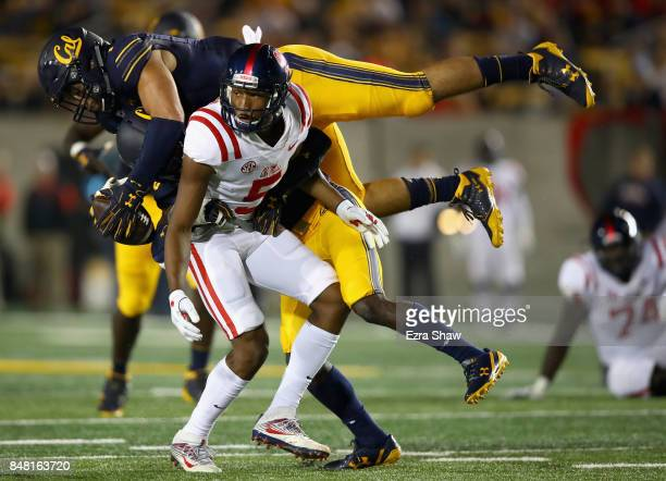 Devante Downs of the California Golden Bears intercepts a pass intended for DaMarkus Lodge of the Mississippi Rebels while Marloshawn Franklin Jr #18...