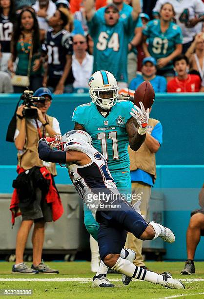 DeVante Parker of the Miami Dolphins catches a pass over Logan Ryan of the New England Patriots during the fourth quarter of the game at Sun Life...