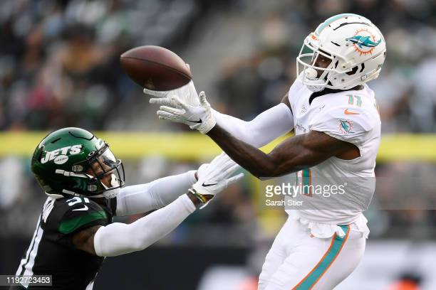 DeVante Parker of the Miami Dolphins catches the ball as Blessuan Austin of the New York Jets defends during the first half of the game at MetLife...