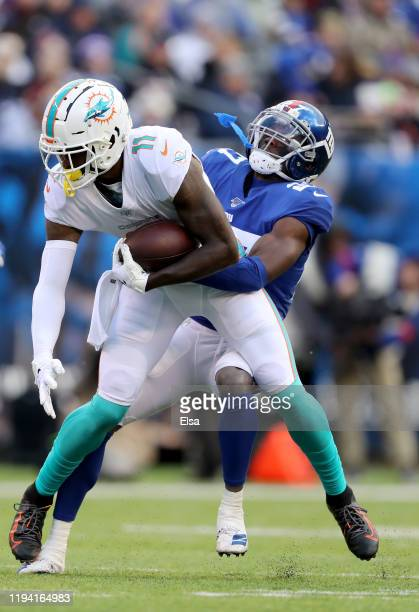 DeVante Parker of the Miami Dolphins makes the catch as Deandre Baker of the New York Giants defends at MetLife Stadium on December 15 2019 in East...