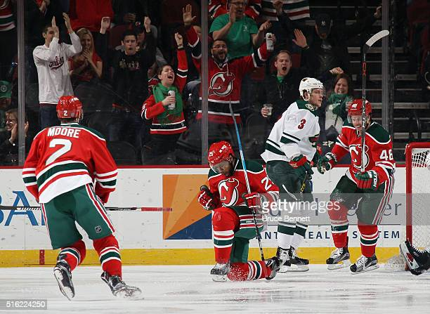 Devante SmithPelly of the New Jersey Devils celebrates his goal at 43 seconds of the first period against the Minnesota Wild and is joined by John...