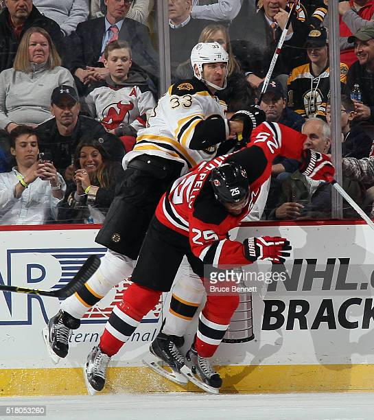 Devante SmithPelly of the New Jersey Devils checks Zdeno Chara of the Boston Bruins into the boards during the third period at the Prudential Center...