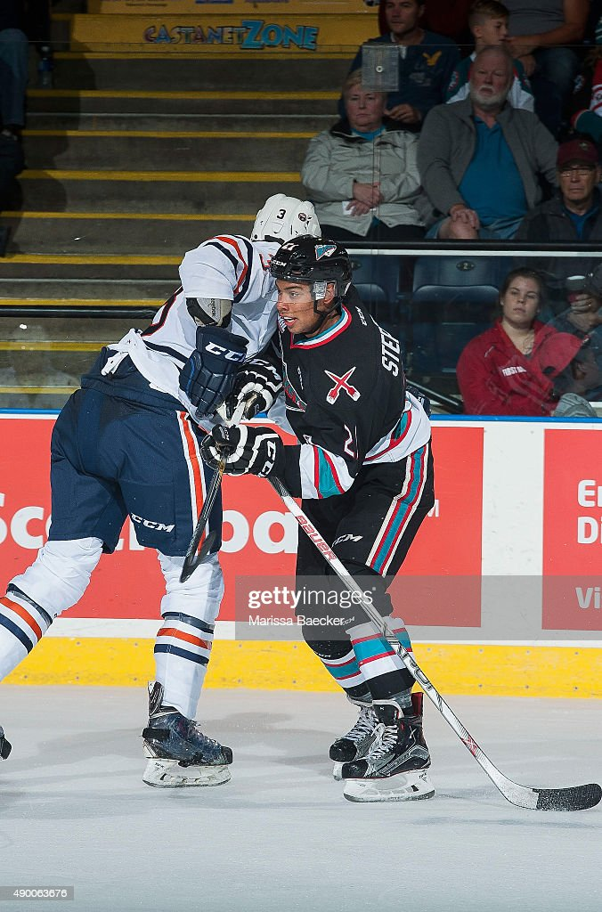 Devante Stephens #21 of the Kelowna Rockets checks a player of the Kamloops Blazers on September 25, 2015 at Prospera Place in Kelowna, British Columbia, Canada.