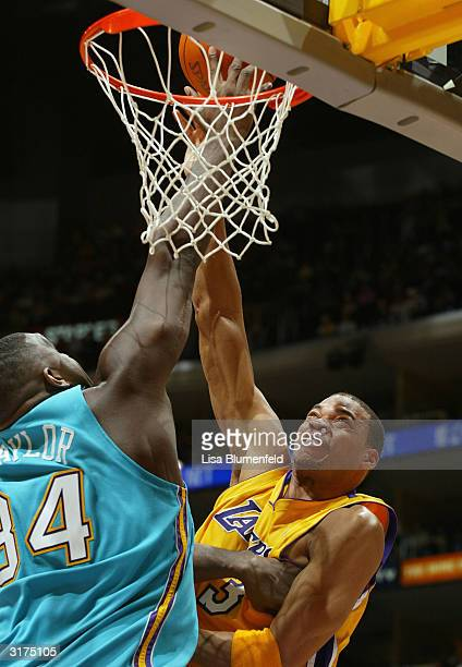 Devean George of the Los Angeles Lakers attempts a shot over Robert Traylor of the New Orleans Hornets during the game at Staples Center on March 30...