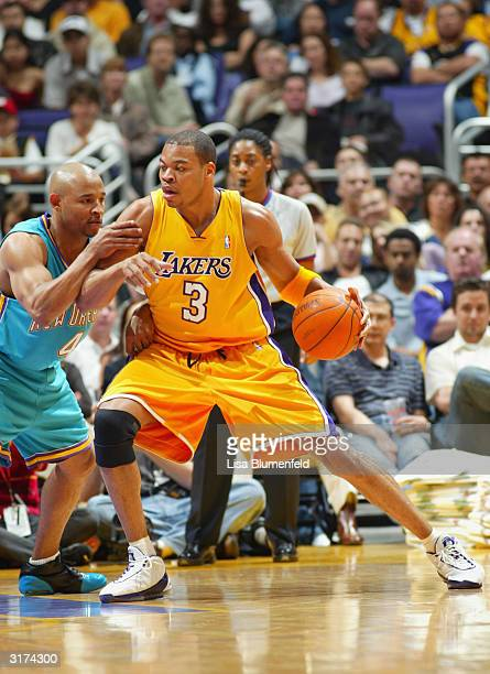 Devean George of the Los Angeles Lakers controls the ball under pressure from David Wesley of the New Orleans Hornets during the game at Staples...