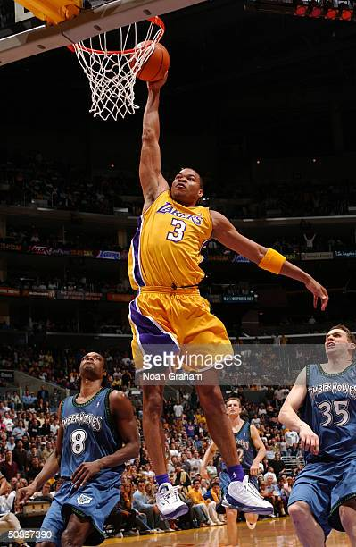 Devean George of the Los Angeles Lakers drives for a dunk attempt past Latrell Sprewell and Mark Madsen of the Minnesota Timberwolves in Game three...