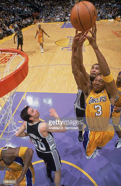 Devean George of the Los Angeles Lakers rebounds over Tim Duncan of the San Antonio Spurs during the NBA game at Staples Center on October 29 2002 in...