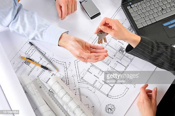 Promoteur donner les clés de la nouvelle maison pour le client, des plans de bâtiment