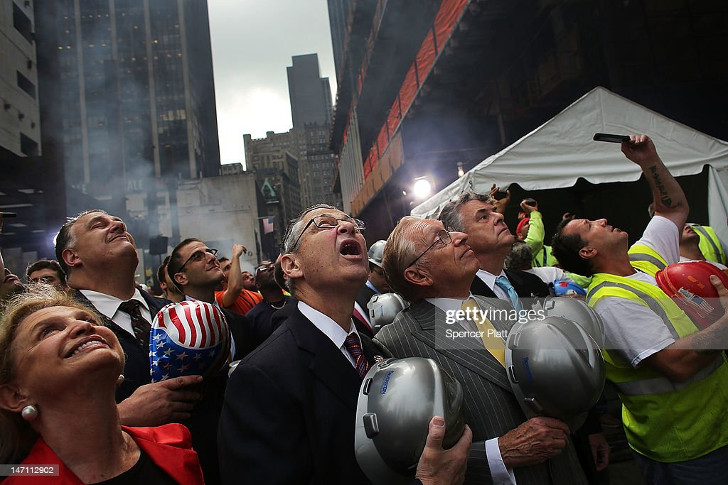 Developer Larry Silverstein (yellow tie) and Assembly Speaker Sheldon Silver (C) watch as the last steel beam, signed by members of the crews that helped build the tower, is hoisted 977 feet to the top of Four World Trade Center on June 25, 2012 in New York City. The trapezoidal glass and steel office building, which is designed as an architectural backdrop to the September 11 Memorial, is scheduled to open in 2013.