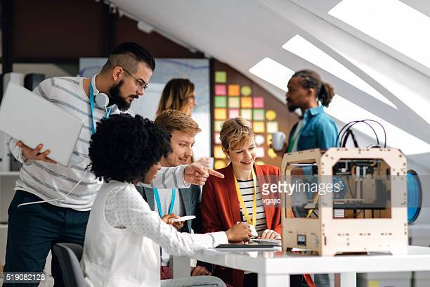 Developer Team Brainstorming by 3D Printer In Their Office.