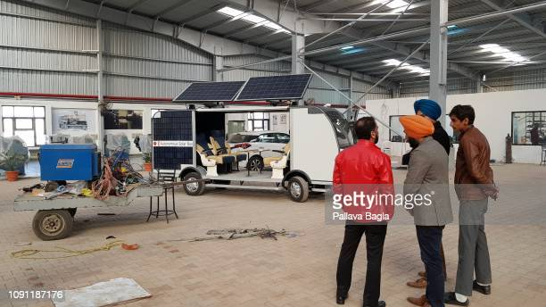 Developers of the bus stand in the workshop where it was fabricated in the university. The worlds first solar powered autonomous or driver less bus...