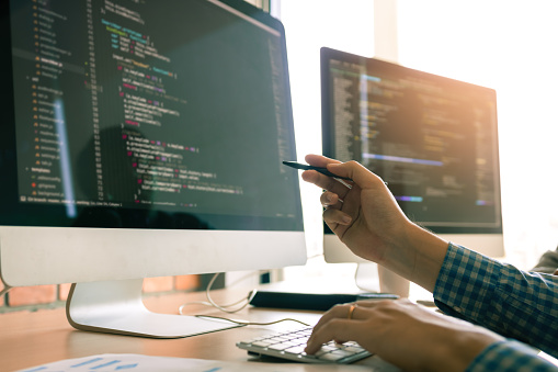 Developing programming working in a software engineers code tech applications on desk in office room. 1128132157