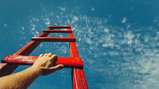 Development Attainment Motivation Career Growth Concept. Mans Hand Reaching For Red Ladder Leading To A Blue Sky 922618410