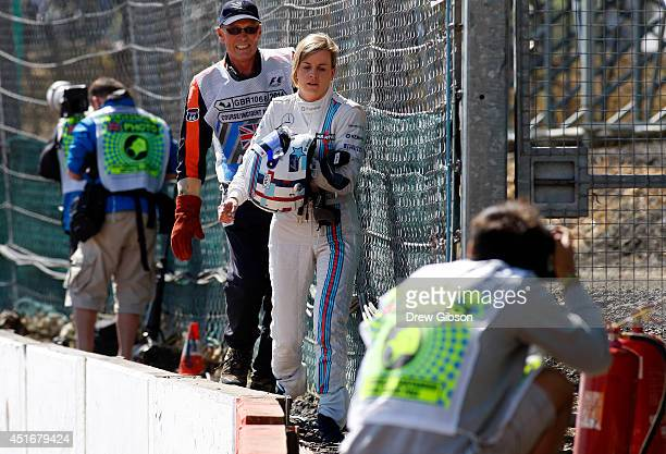 Development driver Susie Wolff of Great Britain and Williams walks back to the garage after experiencing engine problems during practice ahead of the...
