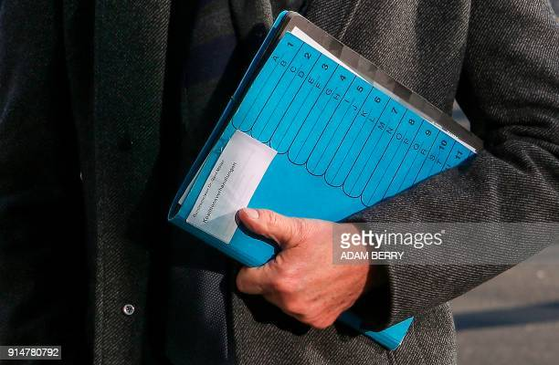Development Minister Gerd Mueller holds a folder reading 'Coalition Negotiations' as he arrives at the Christian Democrats headquarters for further...