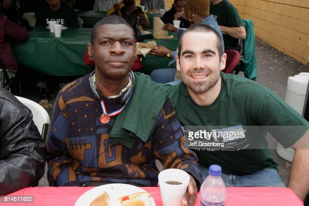 Developmentally disabled man and a volunteer eating food at the Association for Development of Exceptional, MLK Day Carnival.