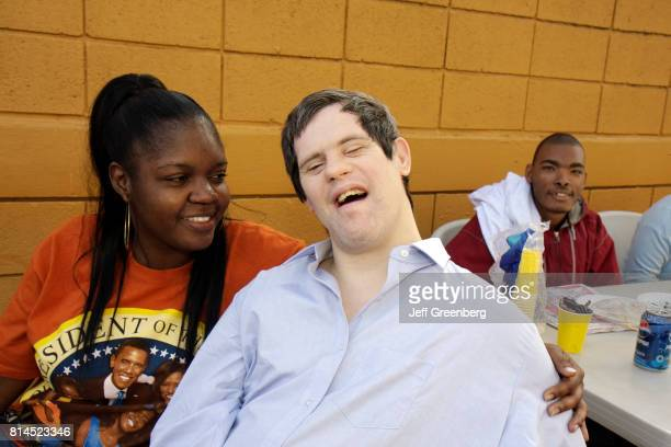 Developmentally disabled man with his mentor at the Association for Development of Exceptional, MLK Day Carnival.