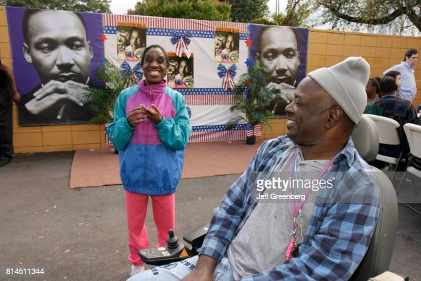 Developmentally disabled woman and a man in a wheelchair at the Association for Development of Exceptional, MLK Day Carnival.