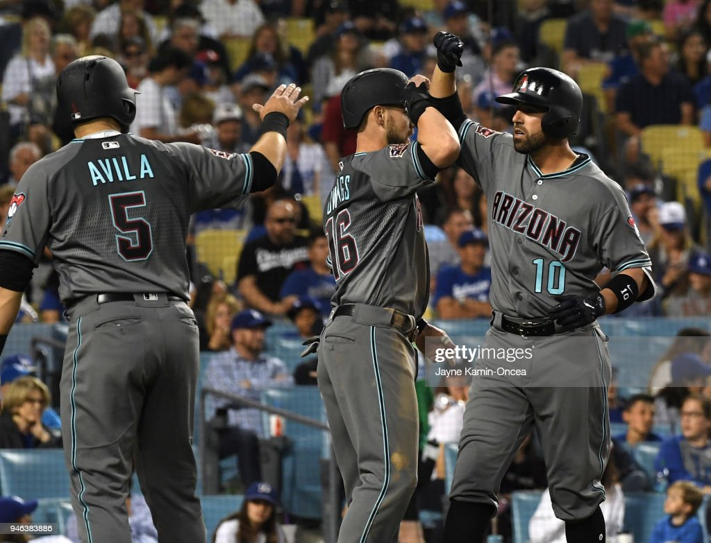 Deven Marrero #10 is greeted by Alex Avila #5 and Chris Owings #16 after scoring on what was thought to be a three run home run by Marrero in the fourth inning of the game at Dodger Stadium on April 14, 2018 in Los Angeles, California. After a challenge of the play was called by the Los Angeles Dodgers, Marrero was called out at second and was given a two-run single because of passing a runner on the bases.