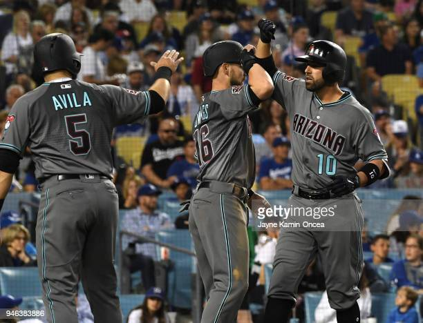 Deven Marrero is greeted by Alex Avila and Chris Owings after scoring on what was thought to be a three run home run by Marrero in the fourth inning...