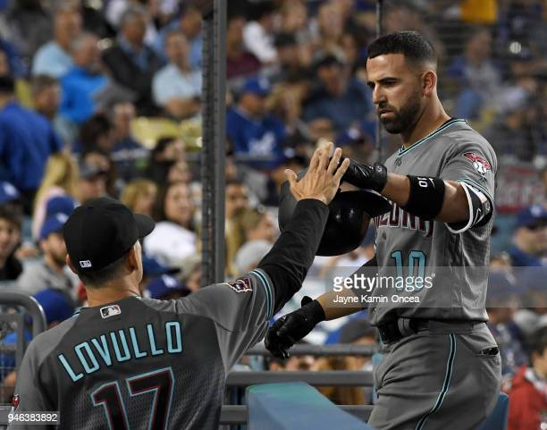 Deven Marrero is greeted by manager Torey Lovullo of the Arizona Diamondbacks after scoring on what was thought to be a three run home run by Marrero...