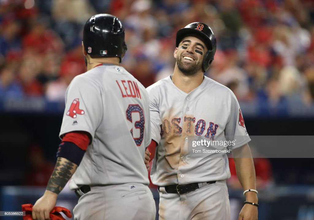 Deven Marrero #17 of the Boston Red Sox celebrates with Sandy Leon #3 after both runners scored on a two-run single by Xander Bogaerts #2 in the ninth inning during MLB game action against the Toronto Blue Jays at Rogers Centre on July 1, 2017 in Toronto, Canada.