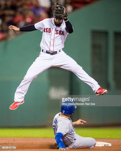 Deven Marrero of the Boston Red Sox leaps after catching a ball to tag out Ryan Goins of the Toronto Blue Jays as he attempts to steal second base...