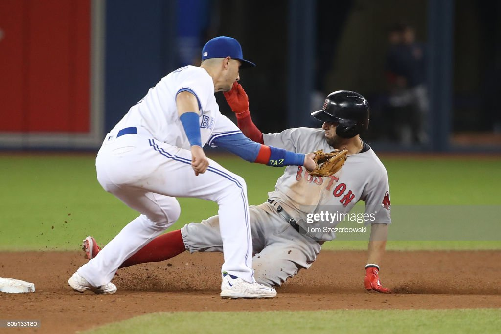 Deven Marrero #17 of the Boston Red Sox slides safely into second base with a two-run double in the eleventh inning during MLB game action as Troy Tulowitzki #2 of the Toronto Blue Jays cannot tag him out in time at Rogers Centre on June 30, 2017 in Toronto, Canada.