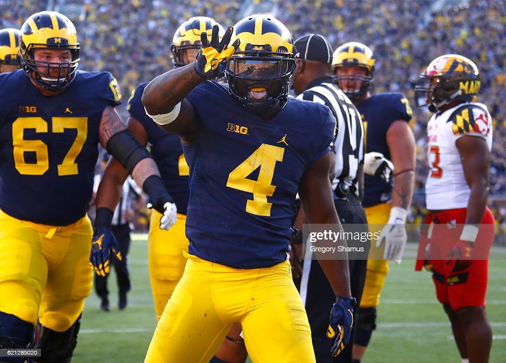 De'Veon Smith #4 of the Michigan Wolverines celebrates a first half touchdown in front of teammate Kyle Kalis #67 while playing the Maryland Terrapins on November 5, 2016 at Michigan Stadium in Ann Arbor, Michigan.