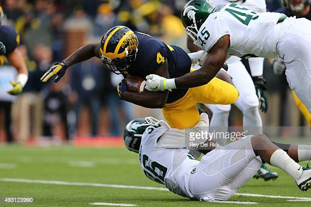 De'Veon Smith of the Michigan Wolverines runs the ball against the Darien Harris of the Michigan State Spartans at Michigan Stadium on October 17,...