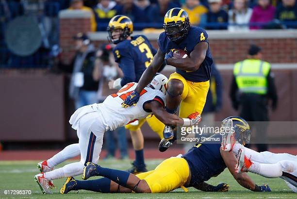 De'Veon Smith of the Michigan Wolverines tires to hurdle the tackle of Darius Mosely of the Illinois Fighting Illini during the third quarter on...