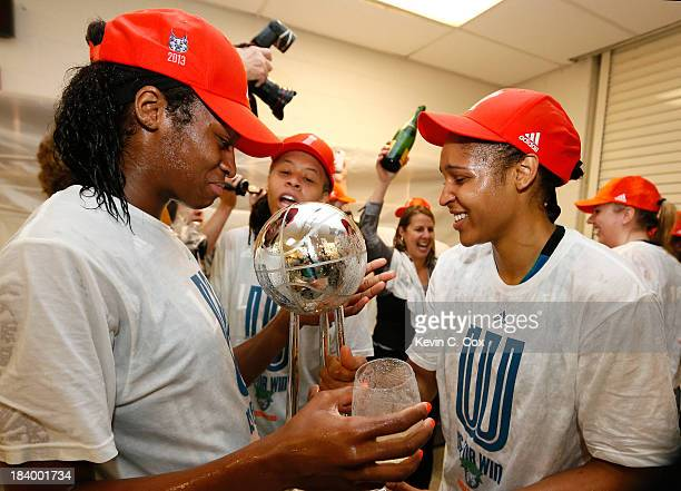 Devereaux Peters Seimone Augustus and Maya Moore of the Minnesota Lynx celebrate with the trophy after their 8677 win over the Atlanta Dream in Game...
