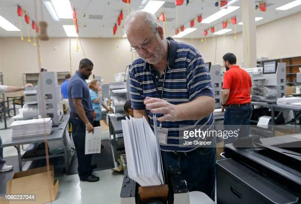 Device is used to straighten ballots before machine counting during a recount at the Broward County Supervisor of Elections office on November 11,...