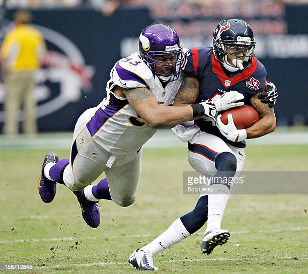 DeVier Posey of the Houston Texans is tackled from behind by Kevin Williams of the Minnesota Vikings at Reliant Stadium on December 23 2012 in...