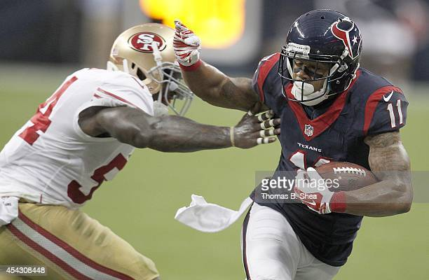 DeVier Posey of the Houston Texans stiff arms Asante Cleveland of the San Francisco 49ers in the first quarter in a preseason NFL game on August 28...