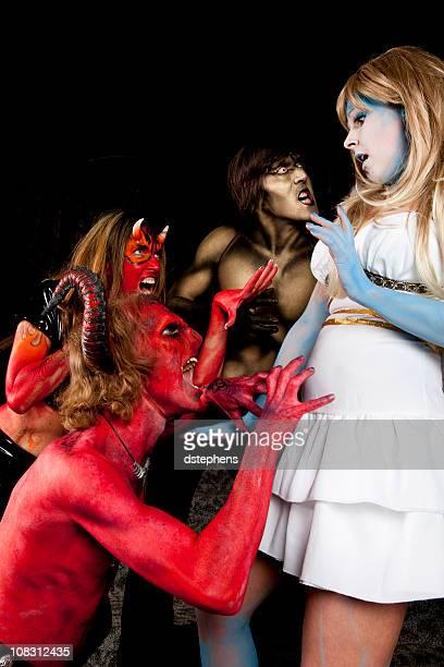 devil y daemons atacando angel - disfraz de diablo fotografías e imágenes de stock