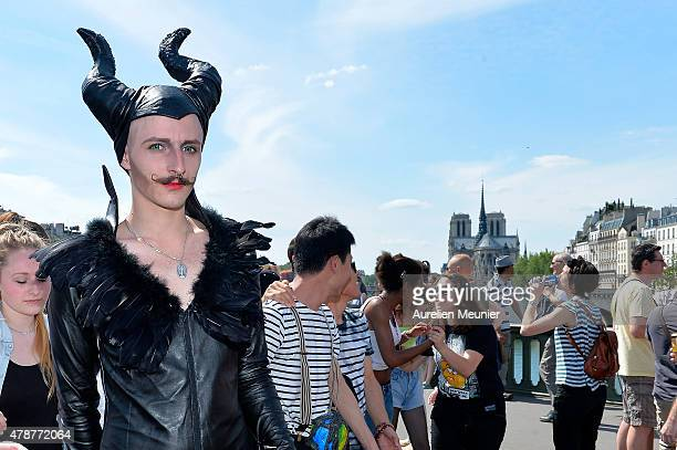 A devil dressed man walks in front of Notre Dame Cathedral as thousands of people gather to support gay rights by celebrating during the Gay Pride...