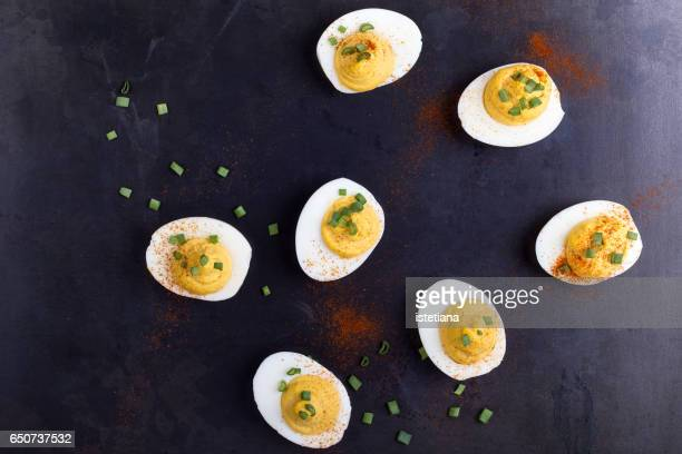 deviled eggs topped with green onion and paprika - hard boiled eggs stock photos and pictures