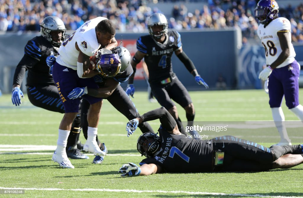Devin Anderson #25 of the East Carolina Pirates has his helmet pulled off by Curtis Akins #7 and La'Andre Thomas #12 of the Memphis Tigers on November 25, 2017 at Liberty Bowl Memorial Stadium in Memphis, Tennessee.
