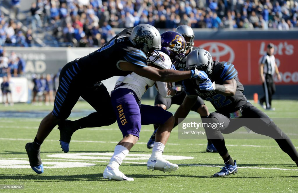 Devin Anderson #25 of the East Carolina Pirates is tackled by Curtis Akins #7 and La'Andre Thomas #12 of the Memphis Tigers on November 25, 2017 at Liberty Bowl Memorial Stadium in Memphis, Tennessee.