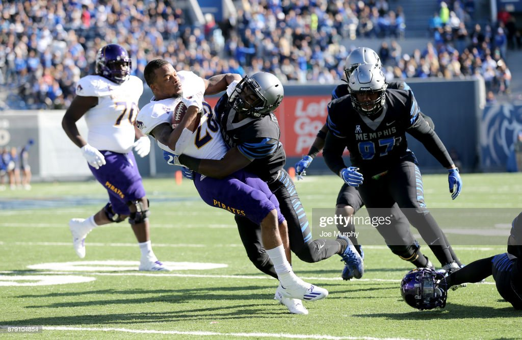 Devin Anderson #25 of the East Carolina Pirates is tackled by La'Andre Thomas #12 of the Memphis Tigers on November 25, 2017 at Liberty Bowl Memorial Stadium in Memphis, Tennessee.
