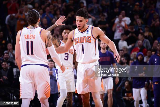 Devin Booker and Ricky Rubio of the Phoenix Suns hifive each other against the Philadelphia 76ers on November 4 2019 at Talking Stick Resort Arena in...