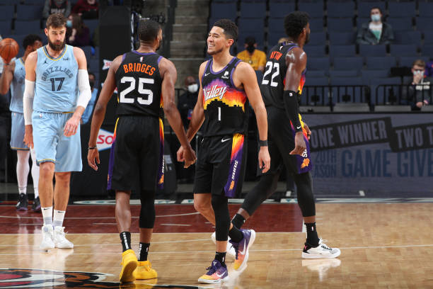 Devin Booker hi-fives Mikal Bridges of the Phoenix Suns during the game against the Memphis Grizzlies on February 20, 2021 at FedExForum in Memphis,...