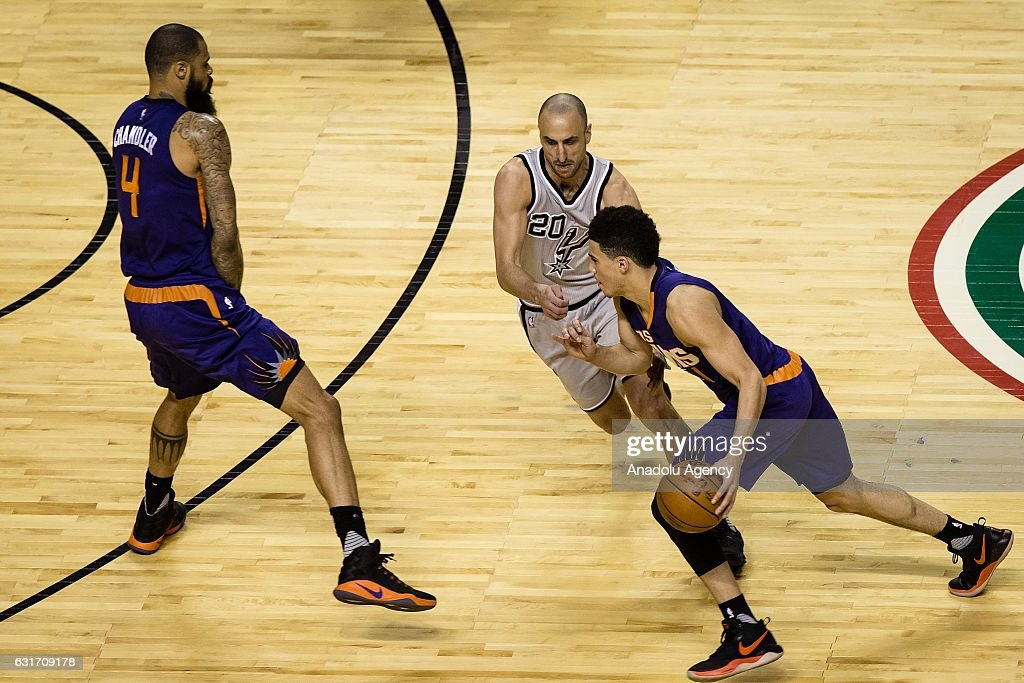 Devin Booker (R) of Phoenix Suns struggle for the ball against Manu Ginobili (C) of San Antonio Spurs during the NBA Game Mexico City between Phoenix Suns and San Antonio Spurs at Arena Ciudad de Mexico, in Mexico City, Mexico on January 14, 2017.