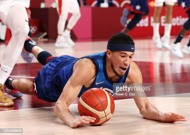 Devin Booker of Team United States dives for a loose ball against Team Spain during the second half of a Men's Basketball Quarterfinal game on day...