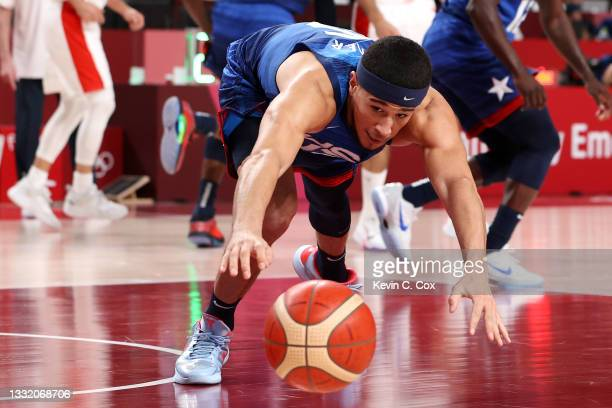 Devin Booker of Team United States reaches for a loose ball against Team Spain during the second half of a Men's Basketball Quarterfinal game on day...