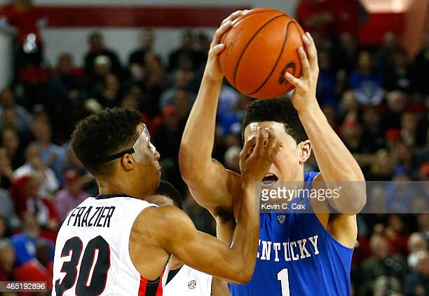 Devin Booker of the Kentucky Wildcats drives into the hand of JJ Frazier of the Georgia Bulldogs at Stegeman Coliseum on March 3 2015 in Athens...