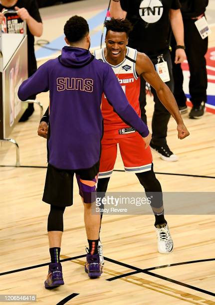 Devin Booker of the Phoenix Suns and Buddy Hield of the Sacramento Kings meet after Hield won the 2020 NBA AllStar MTN DEW 3Point Contest during...